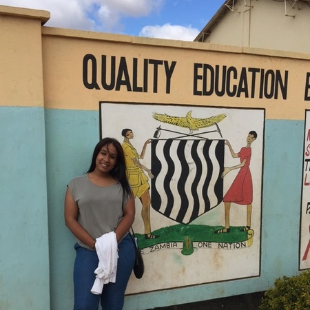 Student posing in front of sign